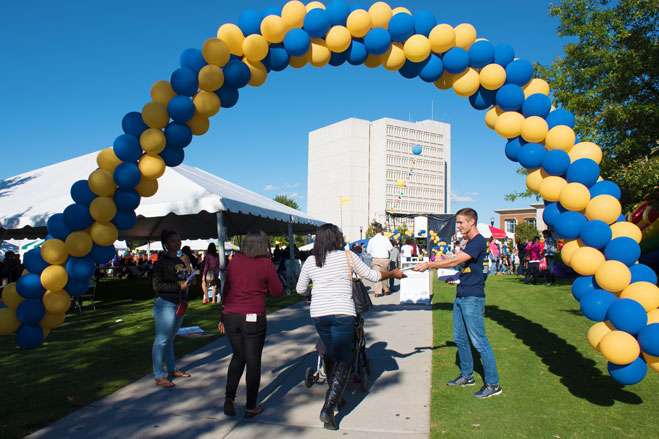 A view of people enjoying Homecoming festivities on Kaplan Commons under a balloon arch