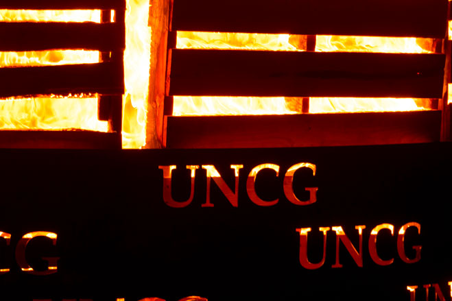 A close-up view of the Homecoming bonfire illuminating the letters UNCG