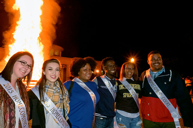 Members of the Homecoming court pose with the bonfire in the background