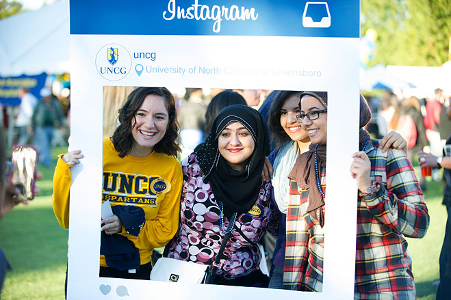 Four people pose with an Instagram frame for a Homecoming photo