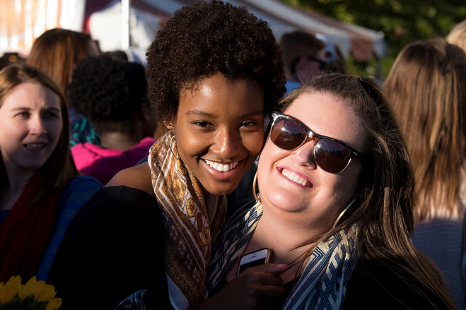 Two friends hug in the Homecoming crowd